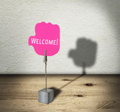 Metal clip holder with welcome note on wooden shelf Stock Photo