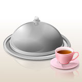 Metal cloche for meal and cup of tea Royalty Free Stock Photography