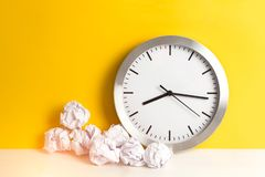 Metal clock with crumpled paper balls on a yellow background and wooden white table. Timing and thinking idea concept. Toned. Metal clock with crumpled paper royalty free stock images