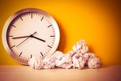 Metal clock with crumpled paper balls on wooden white table. Timing and thinking idea concept. Waste of time concept. Dark toned. Metal clock with crumpled paper royalty free stock image