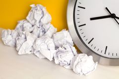 Metal clock with crumpled paper balls on wooden white table. Timing and thinking idea concept. Closedup. Free place for text, copy. Metal clock with crumpled royalty free stock images