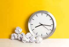 Metal clock with crumpled paper balls on a yellow background and wooden white table. Timing and thinking idea concept. Metal clock with crumpled paper balls royalty free stock photos