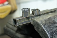. metal clutches in them clamped square tube. there is still a piece on top. shallow depth of cut. Metal clutches in them clamped square tube. there is still a royalty free stock photos