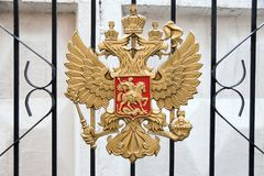 The metal coat of arms of Russia on the gate grill. Against a white wall Royalty Free Stock Photo
