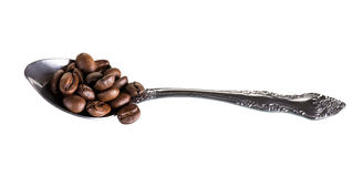 Metal, coffee, grains, spoon. Spoon with coffee beans scattered on a white background Royalty Free Stock Image