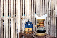 Metal coffee grinder and drip glass pitcher. On old wooden background Royalty Free Stock Photo