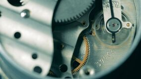 Metal cogs are moving inside of a clockwork mechanism