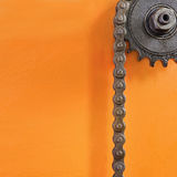 Metal cogwheel and black chain on orange background with empty space. Royalty Free Stock Photo