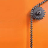Metal cogwheel and chain on orange background with empty space. Royalty Free Stock Image