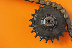 Metal cogwheel and chain on orange background. Royalty Free Stock Photography