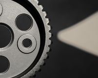 Metal cogwheel and a pointer. Metal car cogwheel a part of timing chain with holes in it on black background stock photo