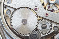 Metal cogwheels inside clockwork. Macro. Stock Images