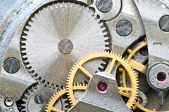 Metal cogwheels inside clockwork. Macro. Stock Images