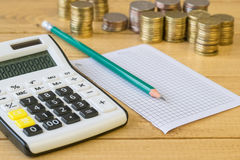 Metal coins and calculator on a rustic table. Stock Image