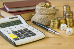 Metal coins and calculator on a rustic table. Royalty Free Stock Image