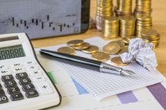 Metal coins and calculator on a rustic table. Royalty Free Stock Photos