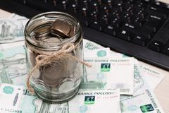 Metal coins in a glass jar against a background of paper denominations of a thousand rubles on the table near the keyboard royalty free stock image