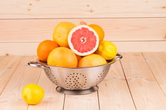 Metal colander full of grapefruits. Royalty Free Stock Images