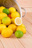 Metal colander full of lemons and limes. Stock Image