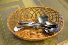 Metal colheres em uma cesta de vime em uma tabela Imagem de Stock