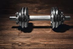 Metal collapsible dumbbell on background. Metal collapsible dumbbell on wooden background Stock Images