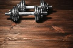 Metal collapsible dumbbells. On wooden background Royalty Free Stock Photos