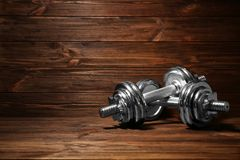 Metal collapsible dumbbells. On wooden background Royalty Free Stock Photography