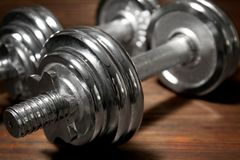 Metal collapsible dumbbells on wooden background. Closeup Stock Photos