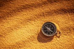 Metal compass on sand. Detail of a metal compass resting on the sand of the desert dunes. Travel concept and desire for adventure stock image