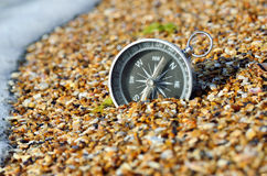 Metal compass in the sand on the seashore. Royalty Free Stock Photos
