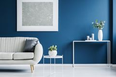 Metal console table with candles. Metal console table with plant in vase and candles standing against blue wall in living room interior with light grey sofa and stock photo