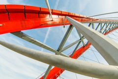 Metal construction of a bridge of red color. Against the sky Stock Photo