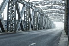 Metal construction of the city bridge on a foggy day in Dieppe, France. Empty asphalt road in the tunnel. Urban scene. City life, transport and traffic concept stock photography