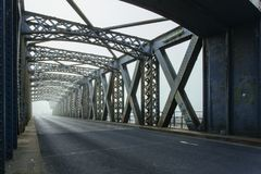 Metal construction of the city bridge on a foggy day in Dieppe, France. Empty asphalt road in the tunnel. Urban scene. City life, transport and traffic concept Stock Photos