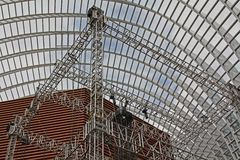 Metal construction in a hangar. Installation of the metal scene for a rock concert in a big glass hangar Royalty Free Stock Photo