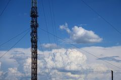 Metal construction of radio tower against the blue sky and white clouds. Metal construction of radio tower against the blue sky royalty free stock photography