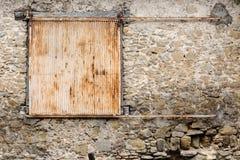 Metal contínuo rústico velho que desliza obturadores na casa de pedra muito velha Foto de Stock
