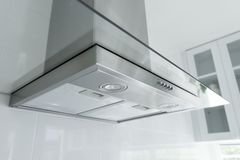 Metal cooker hood in luxury kitchen. Metal cooker hood extractor fan with spotlight in luxury kitchen royalty free stock photography