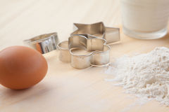 Metal Cookie cutter forms with eggs and flour on wooden table. Together royalty free stock photos