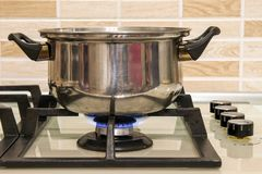 Metal cooking pot standing on kitchen stove with flame. Metal cooking pot standing on kitchen stove with flame Royalty Free Stock Photos