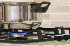 Metal cooking pot standing on kitchen stove with flame. Metal cooking pot standing on kitchen stove with flame Stock Photo