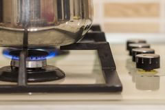 Metal cooking pot standing on kitchen stove with flame. Metal cooking pot standing on kitchen stove with flame Stock Photos