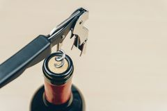 A metal corkscrew or waiter`s friend with a bottle of red wine. Close up of a metal corkscrew or waiter`s friend with a bottle of red wine royalty free stock photo
