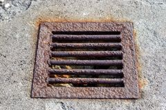 Metal corroded grille for draining water in a concrete floor. A stock photo
