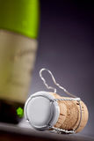 Metal covered cork with wine bottle in background Stock Images