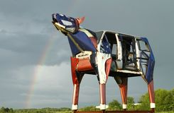 Metal cow with rainbow Royalty Free Stock Images