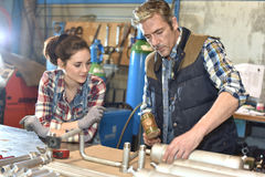 Metal craftsman showing skills to young woman Royalty Free Stock Images