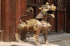 A metal creature guards a building entrance in Patan, Nepal. A metal sculpture of a mythological creature guards a building entrance in the city of Patan, Nepal stock images