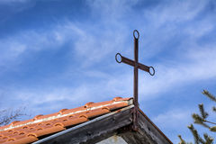 Metal cross on the roof of a house on a blue sky Royalty Free Stock Photos