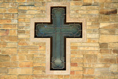Metal cross on textured wall Royalty Free Stock Images